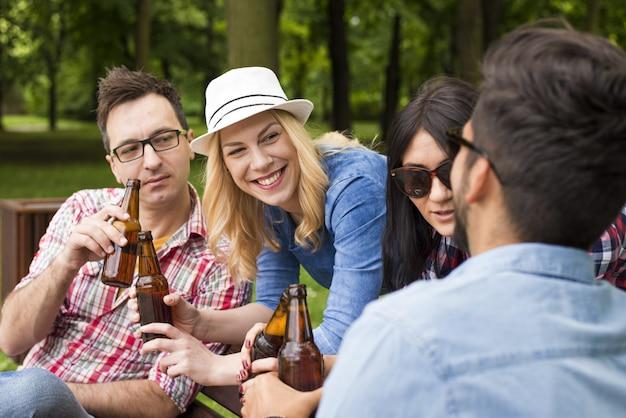 Groupe d'amis caucasiens traîner et boire de la bière sur un banc de parc