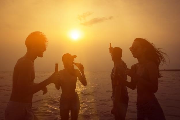 Groupe d'amis célébrant et buvant à la plage au coucher du soleil crépuscule