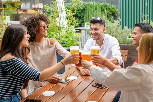 Groupe D'amis Célébrant Dans Un Restaurant En Plein Air Photo Premium