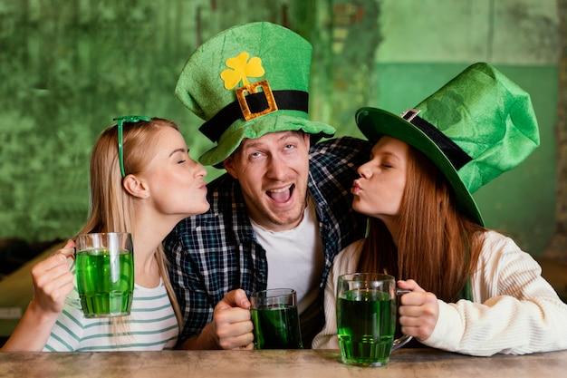 Groupe d'amis célébrant st. patrick's day ensemble au bar