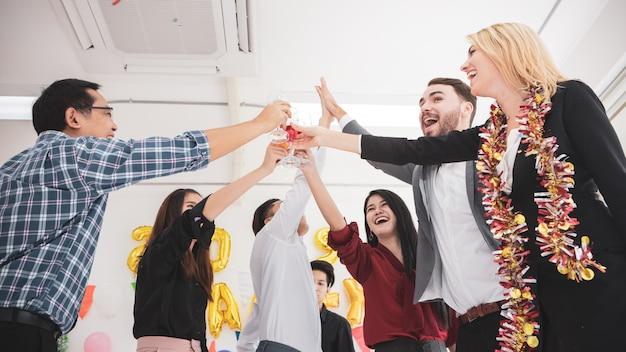 Groupe d'amis célébrant la tenue de flûtes de champagne en dansant.