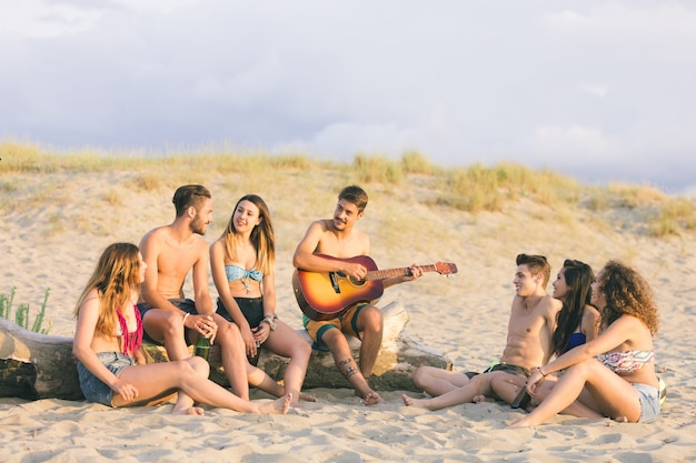 Groupe d'amis chantant sur la plage au coucher du soleil.