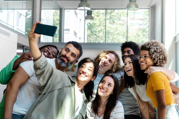 Un groupe d'amis collègues multiraciaux prend un selfie au bureau espace de copie technologie