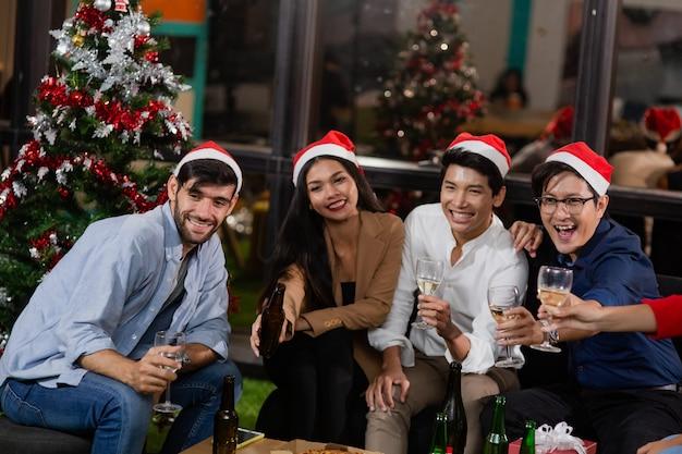 Groupe d'amis ou de collègues de nationalité diversifiée s'amusant avec une fête de noël buvant du champagne et de l'alcool avec un bonnet de noel. un groupe d'amis de diverses nationalités célèbre la fête du nouvel an