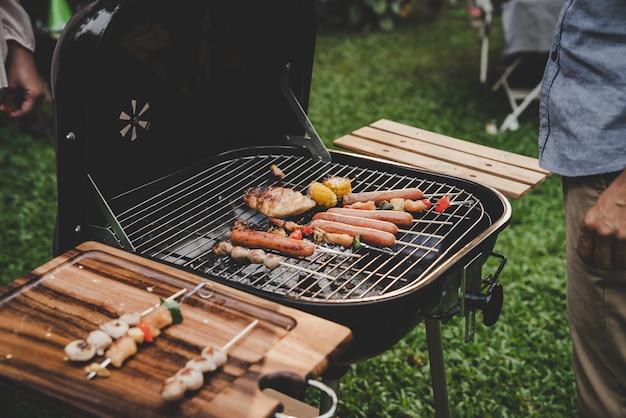 Groupe d'amis de cuisine senior barbecue sur le gril en fête à la maison jardin