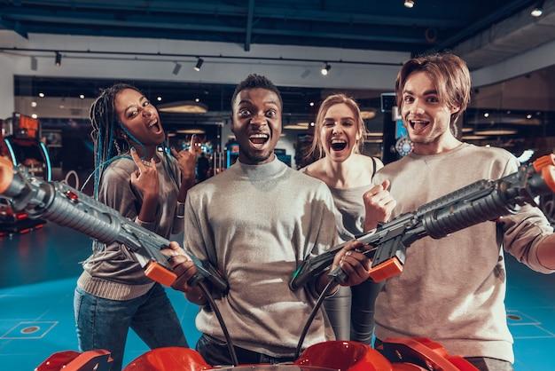 Groupe d'amis dans l'arcade. guy avec des fusils.