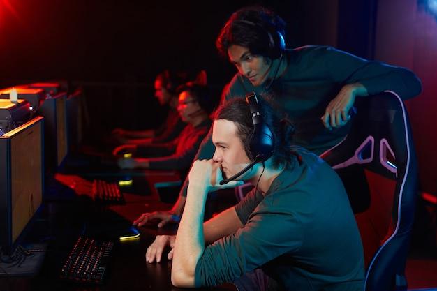 Groupe d'amis dans des écouteurs jouant à des jeux informatiques ensemble en club informatique