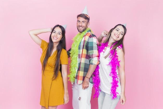 Groupe d'amis dansant sur fond rose