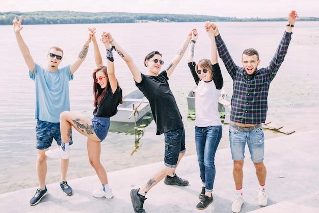 Groupe d'amis debout près du lac en levant la main