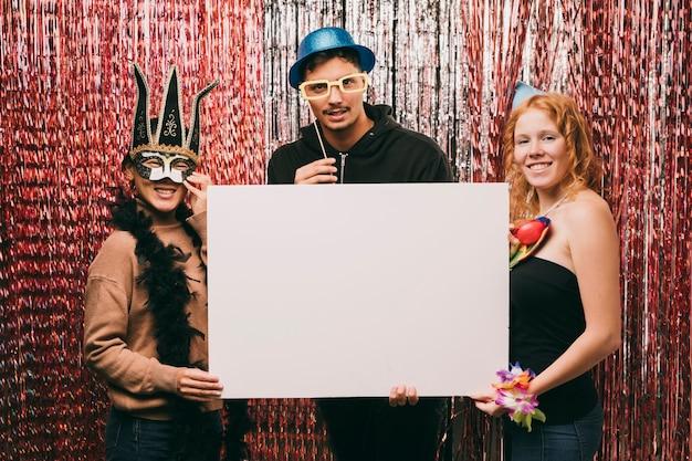 Groupe d'amis déguisés tenant une feuille de papier vierge