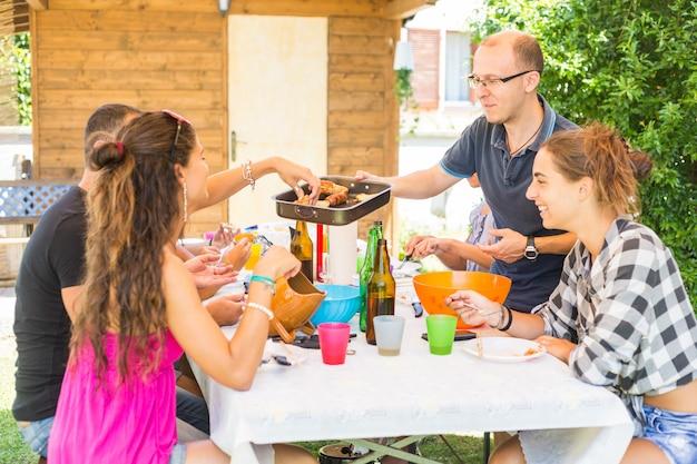 Groupe d'amis déjeunant ensemble dans le jardin
