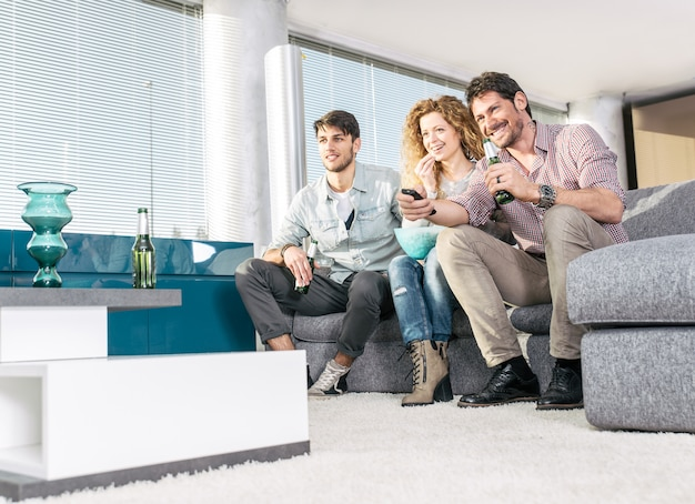 Groupe d'amis devant la télévision dans le salon