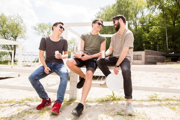 Groupe d'amis discutant sur la clôture de la plage