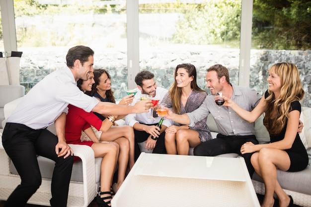 Groupe d'amis discutant et cocktail à la fête