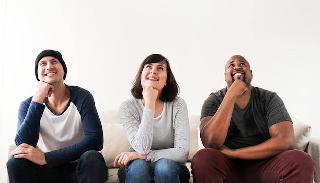 Groupe d'amis divers assis sur un canapé