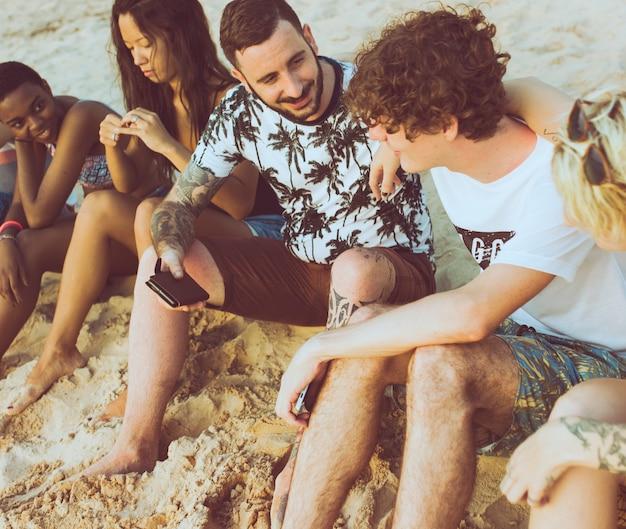 Groupe d'amis divers assis à la plage ensemble