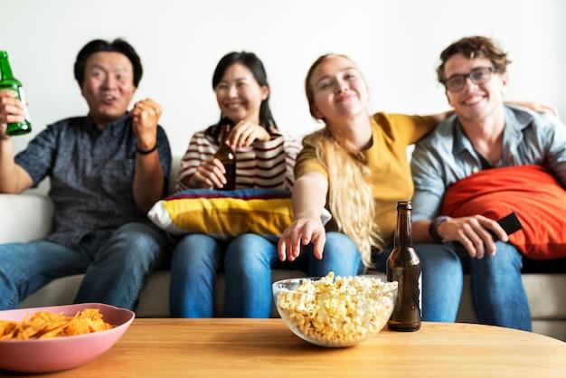 Groupe d'amis divers ayant une soirée cinéma à boire de la bière