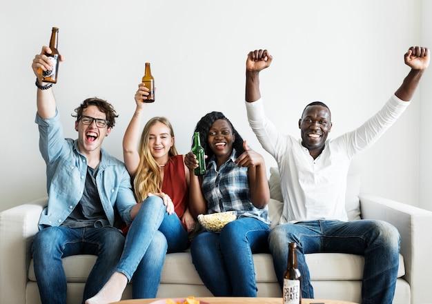 Groupe d'amis divers buvant et acclamant tout en regardant le sport ensemble