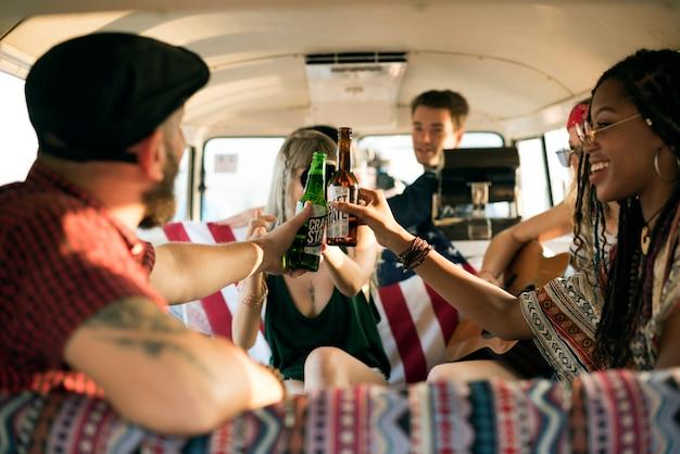 Groupe d'amis divers buvant de la bière ensemble pendant un voyage en voiture