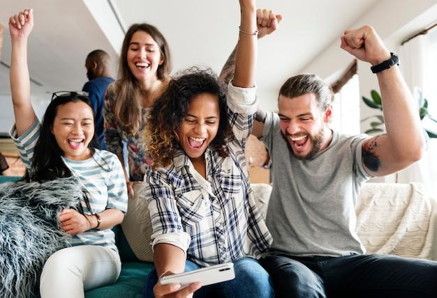 Groupe d'amis divers jouant au jeu sur téléphone mobile