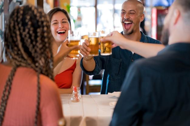 Groupe d'amis divers portant un toast avec des verres à bière tout en savourant un repas ensemble dans un restaurant. notion d'amis.
