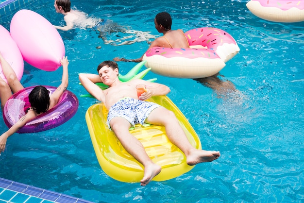 Groupe d'amis divers profiter de la piscine avec des tubes gonflables