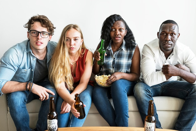 Groupe d'amis divers regardant sérieusement le sport ensemble