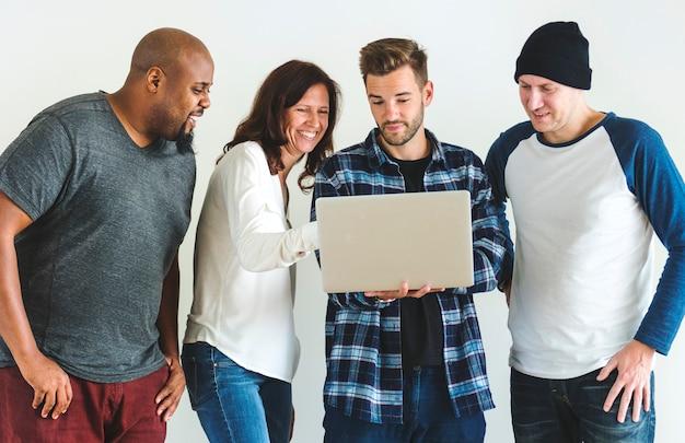Groupe d'amis divers utilisant un ordinateur portable ensemble