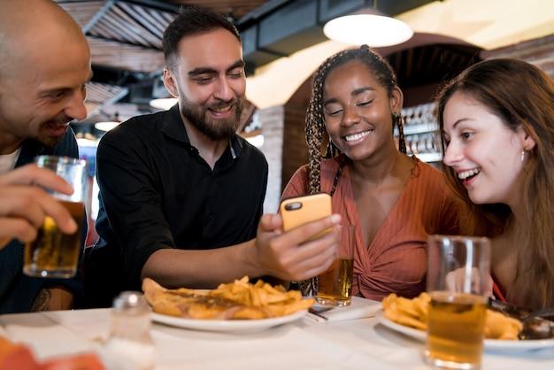 Groupe d'amis divers utilisant un téléphone portable tout en savourant un repas ensemble dans un restaurant. notion d'amis.
