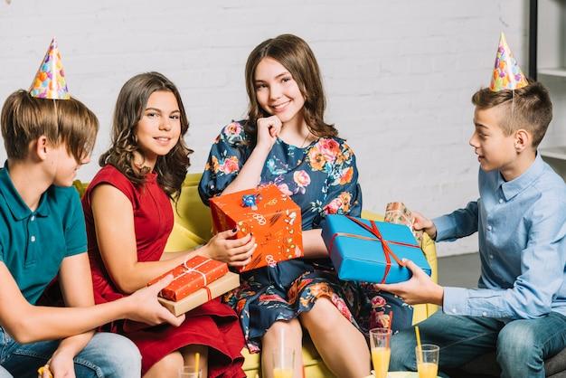 Groupe d'amis donnant des cadeaux emballés à la fille d'anniversaire