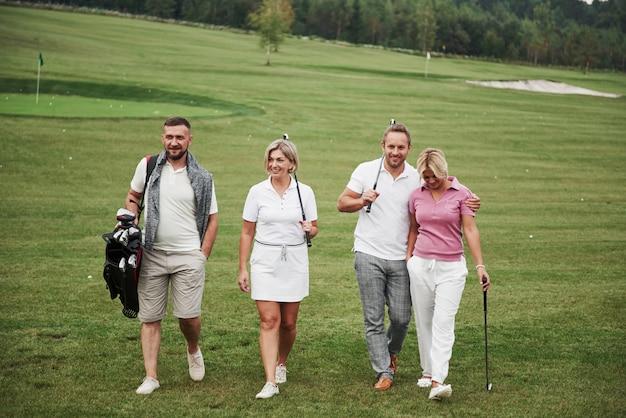Un groupe d'amis élégants sur le parcours de golf apprennent à jouer à un nouveau jeu. l'équipe va se reposer après le match