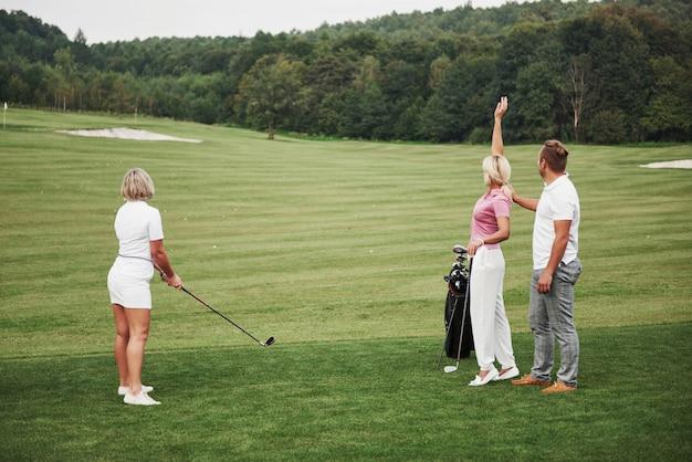 Groupe d'amis élégants sur le parcours de golf apprennent à jouer à un nouveau jeu