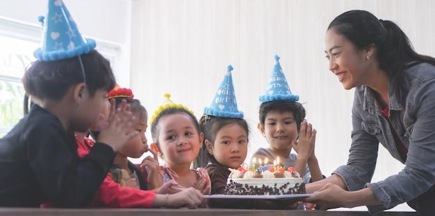 Groupe d'amis d'enfant attend pour souffler le gâteau d'anniversaire
