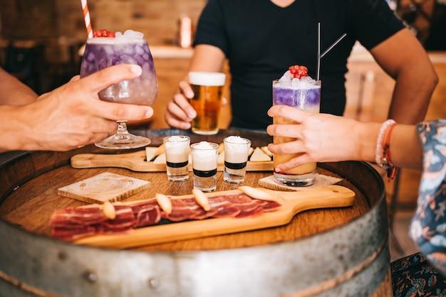 Un groupe d'amis est assis sur la terrasse en été derrière un tonneau en bois avec des cocktails et une collation