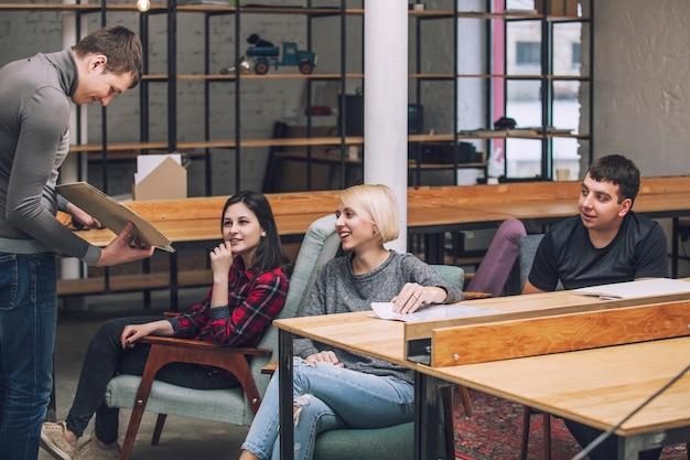 Groupe d'amis étudiants font et discutent des idées créatives dans le loft
