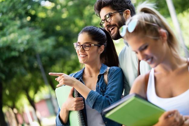Groupe d'amis ou d'étudiants universitaires souriants, se préparant à l'examen à l'extérieur