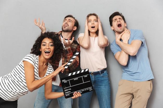 Groupe d'amis excité tenant un clap de tournage.