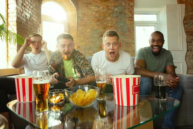 Groupe d'amis excités jouant à des jeux vidéo à la maison. les joueurs masculins ou les fans passent du temps et s'amusent ensemble à la maison