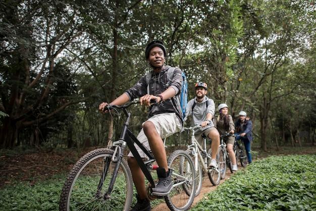 Groupe d'amis faire du vélo de montagne dans la forêt ensemble