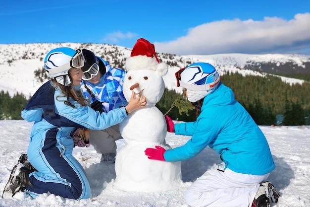 Groupe d'amis faisant un bonhomme de neige à la station de ski.
