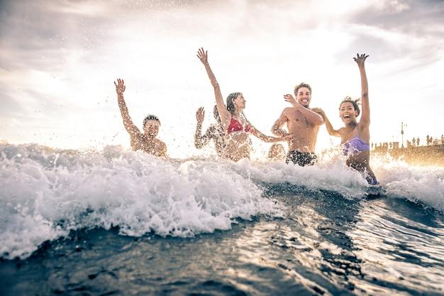 Groupe d'amis faisant une grande fête et des jeux sur la plage
