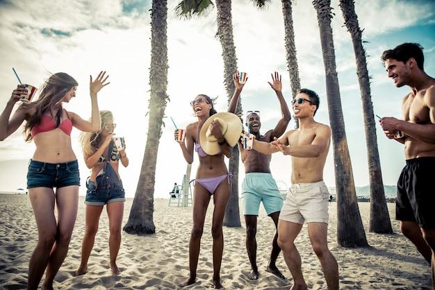 Groupe d'amis faisant une grande fête sur la plage