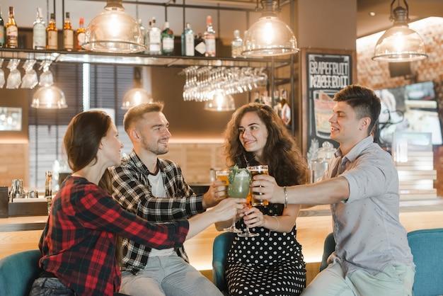 Groupe d'amis faisant griller des boissons au bar