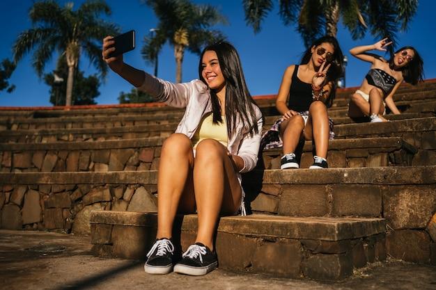 Groupe d'amis faisant le signe «v» dans un selfie en plein air.