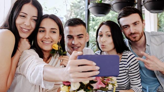 Un groupe d'amis fait des selfies dans un café