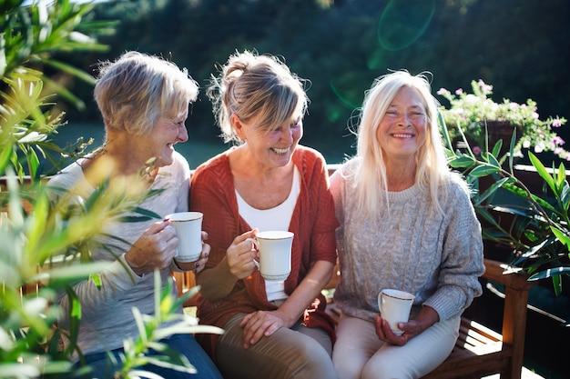 Groupe d'amis femmes âgées avec café assis à l'extérieur sur la terrasse, se reposant.