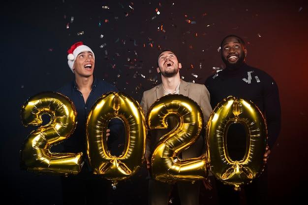 Groupe d'amis à la fête du nouvel an posant