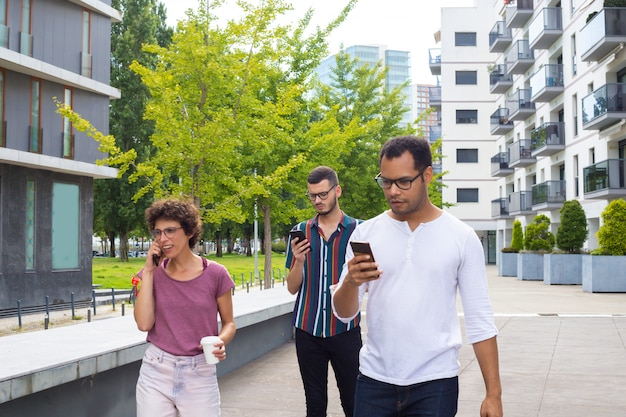 Groupe d'amis avec des gadgets se promener à l'extérieur