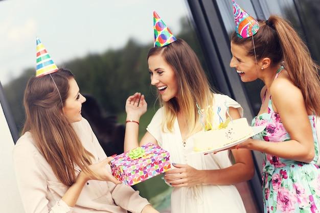 Groupe d'amis avec gâteau et cadeaux célébrant l'anniversaire