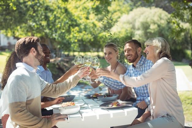 Groupe d'amis, grillage, verres de vin dans un restaurant